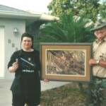 "2008 Grand prize winner Loretta Castonguag receives her "" Florida Treasures"" painting from Bill Samuels of the Florida Panther Project."